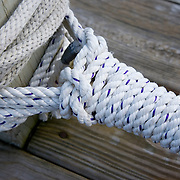 White rope tied into a long running wrap and knot on a post that is part of a float and dock. Rockland. Maine