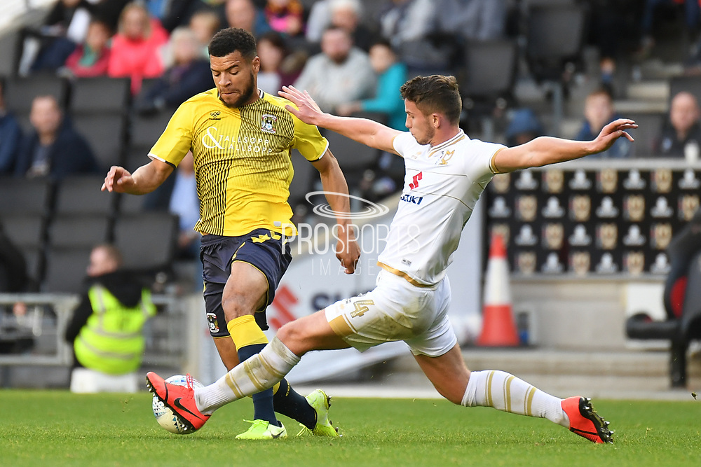 Milton Keynes Dons midfielder Jordan Houghton (24) comes in to tackle Coventry City striker Max Biamou (9) during the EFL Sky Bet League 1 match between Milton Keynes Dons and Coventry City at stadium:mk, Milton Keynes, England on 19 October 2019.