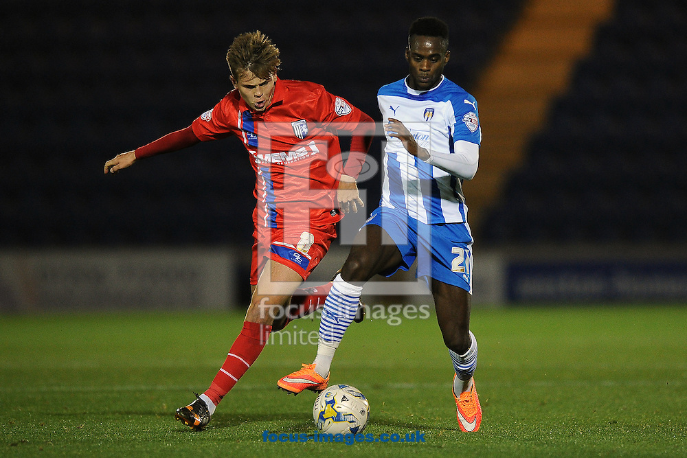 Gavin Massey of Colchester United looks to get past Jake Hessenthaler of Gillingham during the Johnstone's Paint Trophy match between Colchester United and Gillingham at the Weston Homes Community Stadium, Colchester<br /> Picture by Richard Blaxall/Focus Images Ltd +44 7853 364624<br /> 07/10/2014