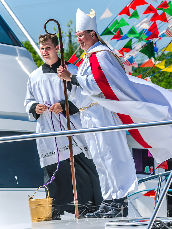 Seminarian Joey Dunbar and Catholic Archbishop Thomas J. Rodi stand on the deck of a boat and wait to bless passing boats with Holy Water during the 65th annual Blessing of the Fleet in Bayou La Batre, Alabama, May 4, 2014. The first fleet blessing was held by St. Margaret's Catholic Church in 1949, carrying on a long European tradition of asking God's favor for a bountiful seafood harvest and protection from the perils of the sea. The highlight of the event is a blessing of the boats by the local Catholic archbishop and the tossing of a ceremonial wreath in memory of those who have lost their lives at sea. The event also includes a land parade and a parade of decorated boats that slowly cruise through the bayou. (Photo by Carmen K. Sisson/Cloudybright)