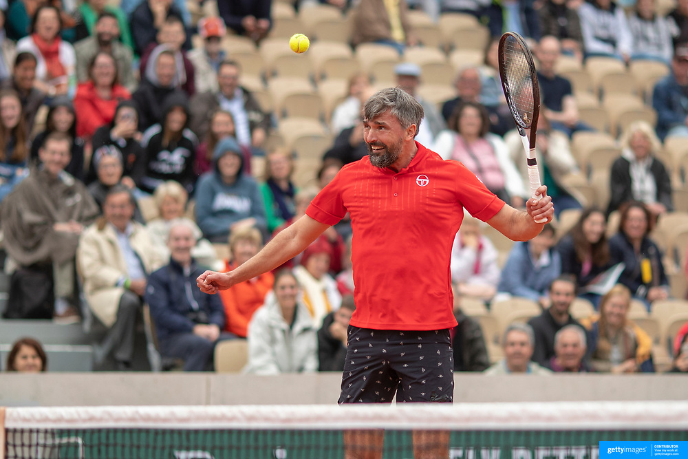 PARIS, FRANCE June 05. Goran Ivanisevic of Croatia heads the ball while playing with  Sergi Bruguera of Spain against Mansour Bahrami of France and Fabrice Santoro of France on Court Simonne-Mathieu during the Men's Legends over 45 competition at the 2019 French Open Tennis Tournament at Roland Garros on June 5th 2019 in Paris, France. (Photo by Tim Clayton/Corbis via Getty Images)