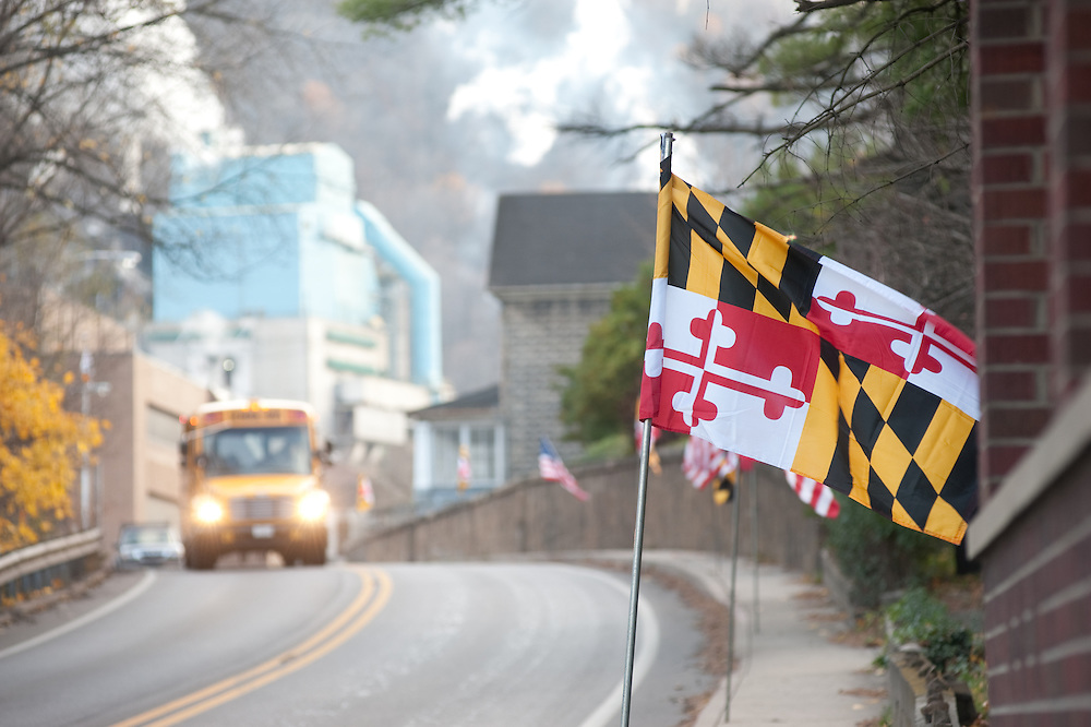 School bus driving down the road with Maryland flag