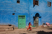 A local girl in red runs past a blue painted house in a village near Medinet Habu on the West Bank of Luxor, Nile Valley, Egypt.