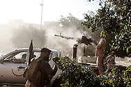 A Libyan rebel from Misrata fires it's machine gun at buildings where loyalist snipers are holed up in Abu Salim district. Rebels say they control most of Tripoli, but two days after they surged in the city, they faced pockets of fierce resistance from regime loyalists. 25 August 2011.