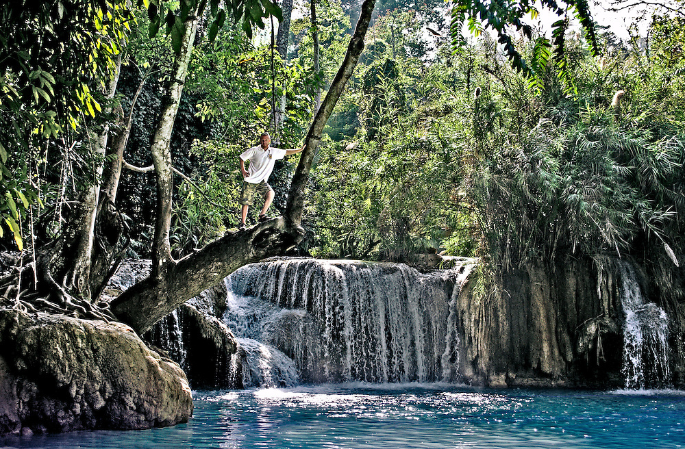Young blond man perched on a tree branch overhanging a waterfall in Laos.
