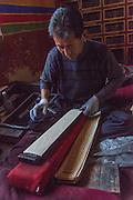 China, Tibet, Lhasa. Sera Monastery. Printing press. Man hand printing Buddhist prayers.