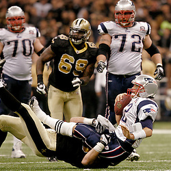 2009 November 30: New England Patriots quarterback Tom Brady (12) is tackled by New Orleans Saints linebacker Scott Fujita (55) during a 38-17 win by the New Orleans Saints over the New England Patriots at the Louisiana Superdome in New Orleans, Louisiana.