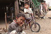 Young children who live in a squatter's slum in Kampong Cham, Cambodia, while away the day in front of a home. They are among 250 people, who were displaced to this location from their former homes on the banks of the Mekong, River. The move was triggered by the construction of a large new hotel on the site of their former homes.  In all, thirty-nine families made the move and each received 50 kilograms of rice and plastic sheeting to wrap up their homes from the new hotel's owner.