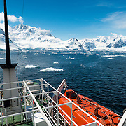 An Antarctic cruise ship heads towards the moutnainous shore of the Antarctic Peninsula, as seen from the top deck of the ship, with one of the ship's lifeboats in the bottom right.