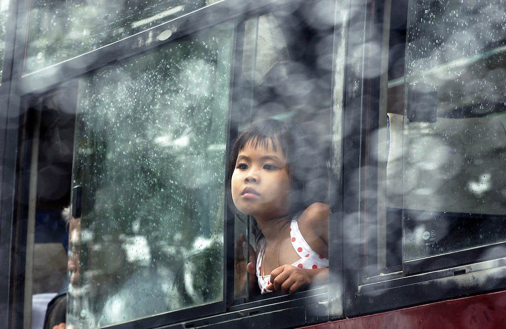 A girl looks out the rain soaked window of bus which is stuck in a traffic jam waiting to cross the ferry at Can Tho on the Mekong Delta in Vietnam..