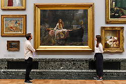 "© Licensed to London News Pictures. 05/09/2018. LONDON, UK.  Staff members view ""The Lady of Shalott"", 1888, by John William Waterhouse, at Tate Britain, to mark the launch of a major new exhibition at the National Gallery of Australia (NGA) in December 2018.  Over forty Pre-Raphaelite works will be loaned by Tate to NGA, which have never been shown in Australia until now, including ""Ophelia"", 1851-52, by John Everett Millais and ""The Lady of Shalott"", 1888, by John William Waterhouse.  Photo credit: Stephen Chung/LNP"