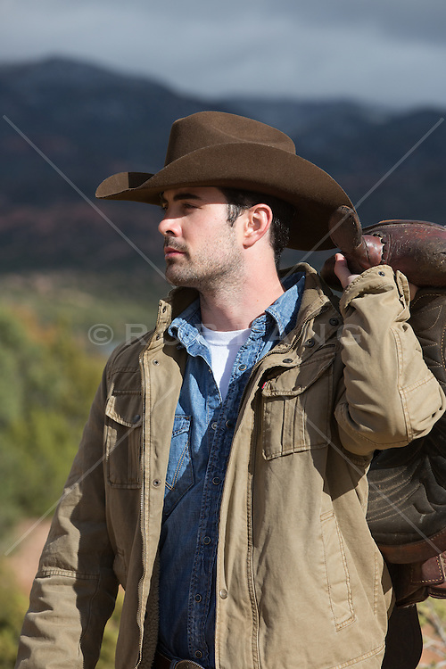 cowboy walking with a saddle outdoors
