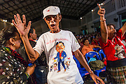 27 JULY 2013 - BANGKOK, THAILAND:  A Thai Red Shirt wearing a Thaksin Shinawatra tee shirt, dances during the party for Thaksin Shinawatra. The Red Shirts celebrated former Prime Minister Thaksin Shinawatra's 64th birthday with a party at Phibun Prachasan School in Bangkok. They had a Buddhist Merit Making Ceremony, dinner, cake and entertainment. Most of the Red Shirt political elite traveled to Hong Kong for a party with Thaksin. Thaksin, the former Prime Minister, was deposed by a coup in 2006 and subsequently convicted of corruption related crimes. He went into exile rather than go to jail but remains very popular in rural parts of Thailand. His sister, Yingluck Shinawatra is the current Prime Minister and was elected based on her brother's recommendation.    PHOTO BY JACK KURTZ