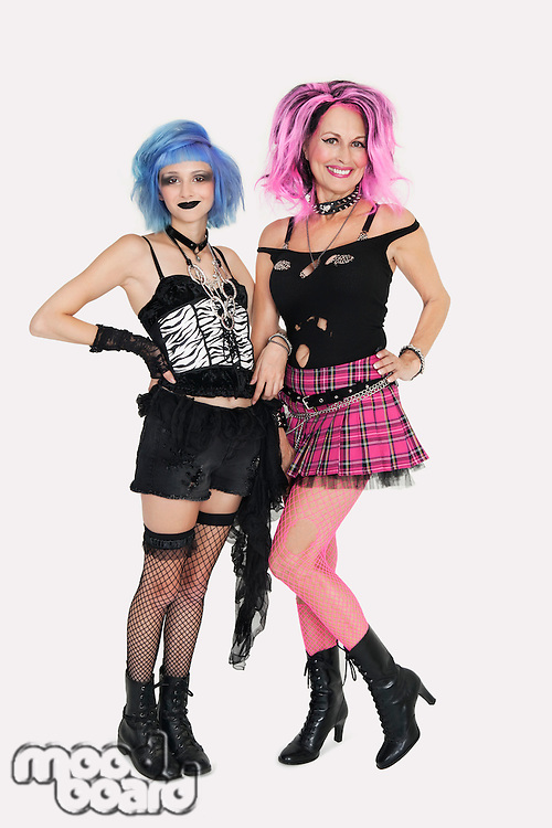 Portrait of happy senior and young punk females standing over gray background