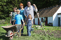 Parents with three children (5-9) gardening outside cottage portrait
