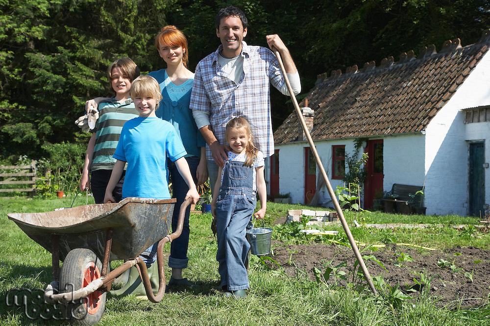 Parents with three children (5-9) gardening outside cottage portrait