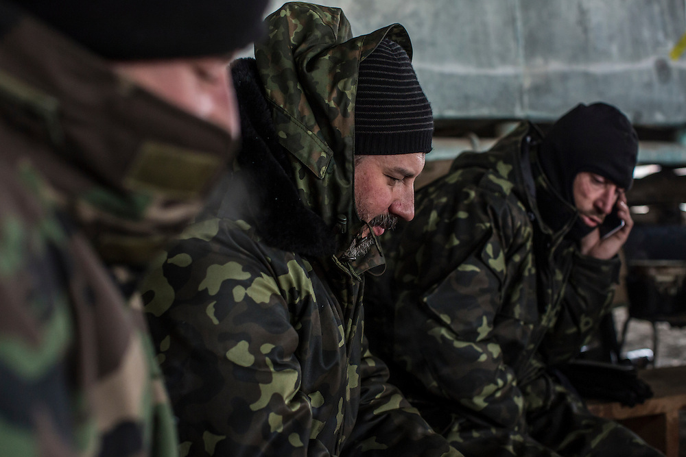 PERVOMAISKE, UKRAINE - NOVEMBER 18, 2014: A man who goes by the name Padre, center, of the 5th platoon of the Dnipro-1 brigade, a pro-Ukraine militia, and other platoon members sit by the fire to keep warm at their post underneath a bridge in Pervomaiske, Ukraine. CREDIT: Brendan Hoffman for The New York Times