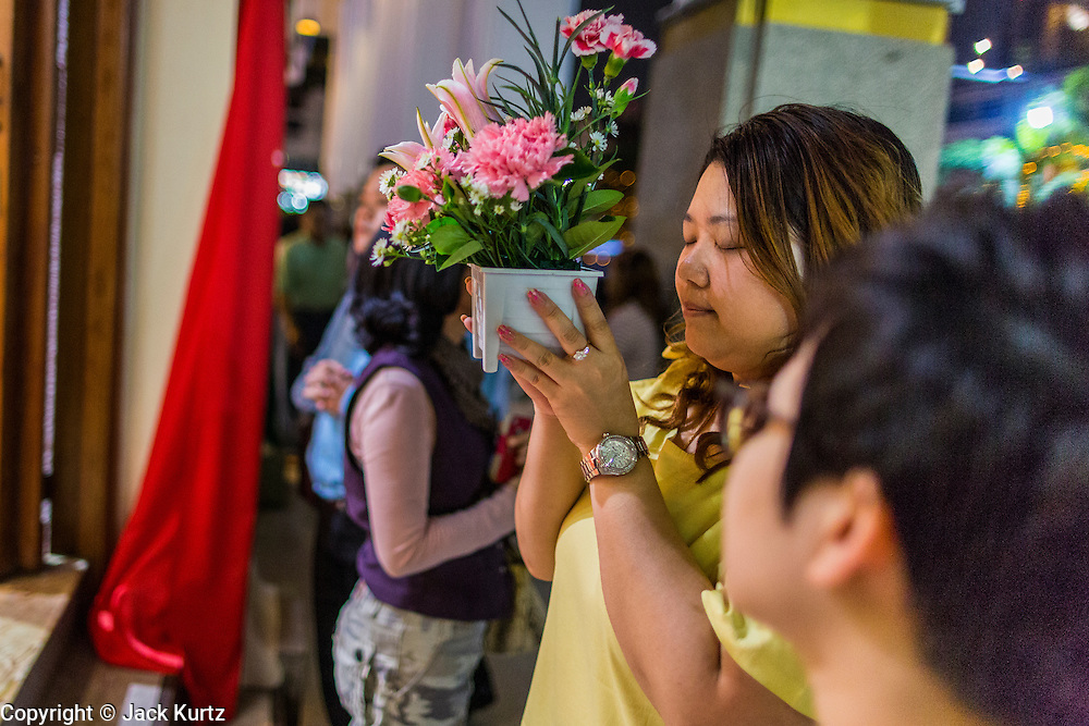 24 DECEMBER 2013 - BANGKOK, THAILAND: A woman prays before leaving flowers as a donation during Christmas services at Holy Redeemer Church in Bangkok. Thailand is predominantly Buddhist but Christmas is widely celebrated throughout the country. Buddhists mark the day with secular gift giving but there are about 300,000 Catholics in Thailand who celebrate religious Christmas. Catholics first came to Thailand (then Siam) in 1567 as chaplain for Portuguese mercenaries in the employ of the Siamese monarchy. There has been a continuous Catholic presence in Thailand since then.   PHOTO BY JACK KURTZ