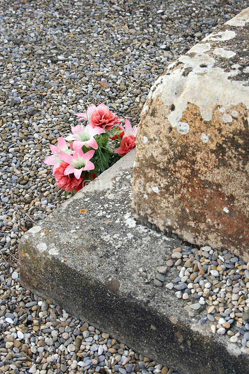 plastic flowers in front of an old gravestone