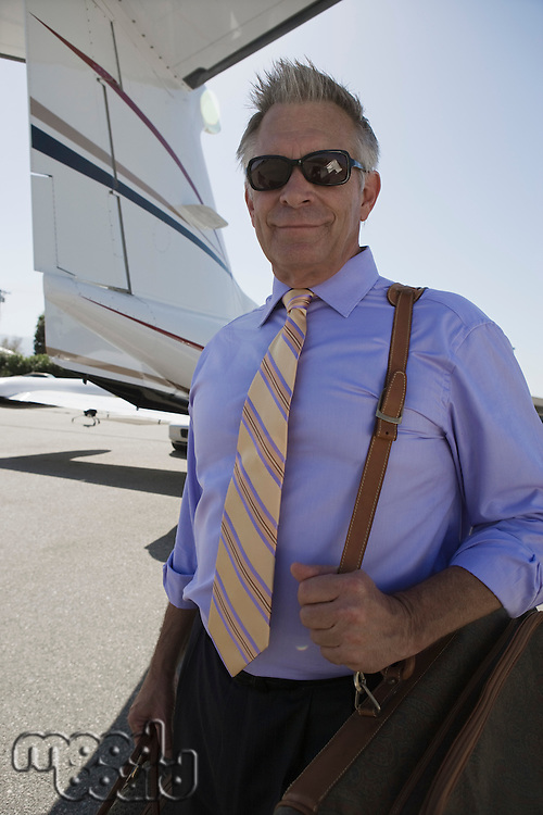 Senior businessman standing in front of private airplane.