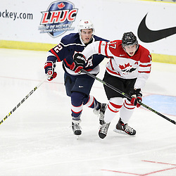 COBOURG, - Dec 15, 2015 -  Game #5 - Canada West vs the United States at the 2015 World Junior A Challenge at the Cobourg Community Centre, ON. Ross Colton #22 of Team United States and Tyler Busch #17 of Team Canada West pursues the play during the first period.(Photo: Tim Bates / OJHL Images)