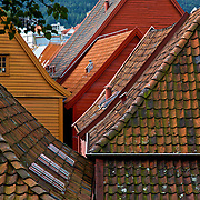 Bryggen (Norwegian for the Wharf), also known as Tyskebryggen (the German Wharf) is a series of Hanseatic commercial buildings lining the eastern side of the fjord coming into Bergen, Norway. Bryggen has since 1979 been on the UNESCO list for World Cultural Heritage sites. Seen from the back, here, the tightly packed rooftops provide rich color and texture.