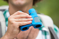 Close-up of male hiker holding binoculars