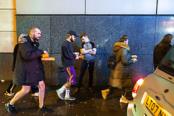 """© Licensed to London News Pictures . 23/12/2017. Manchester, UK. A man stands by a taxi rank with his trousers open . Revellers out in Manchester City Centre overnight during """" Mad Friday """" , named for being one of the busiest nights of the year for the emergency services in the UK . Photo credit: Joel Goodman/LNP"""