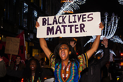 "London, November 26th 2014. A vigil for teenager Mike Brown who was shot dead by a policeman in Ferguson, Missouri this year, takes place outside the US embassy in London. Anti-racism and human rights campaigners called the 'emergency' protest following a court verdict that clears Police Officer Darren Wilson of murder. PICTURED: A woman's placard matches the crowd's chant ""Black lives matter!"""