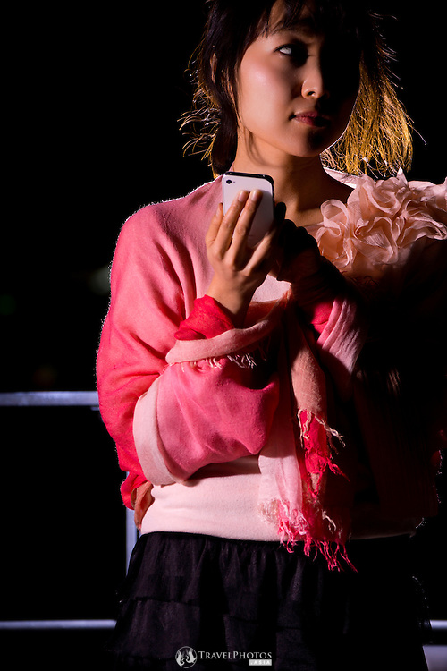 Outdoor night portraits of a young Japanese lady using her smart phone.