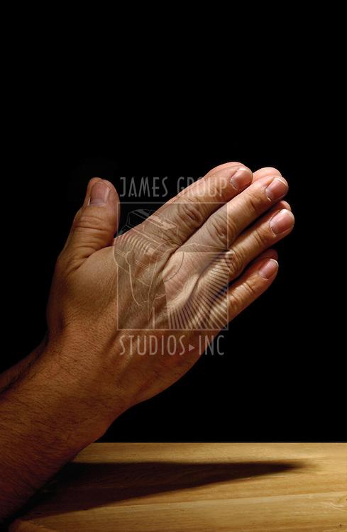 man's praying hands on dark background