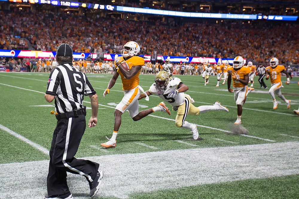 Tennessee Volunteers wide receiver Marquez Callaway (1) carries the ball for a touchdown past Georgia Tech Yellow Jackets defensive back A.J. Gray (5) during the second half of the Chick-fil-A Kickoff NCAA football game on Monday, September 4, 2017, in Atlanta. Tennessee won in two overtimes, 42-41. (Paul Abell via Abell Images for Chick-fil-A Kickoff Game)