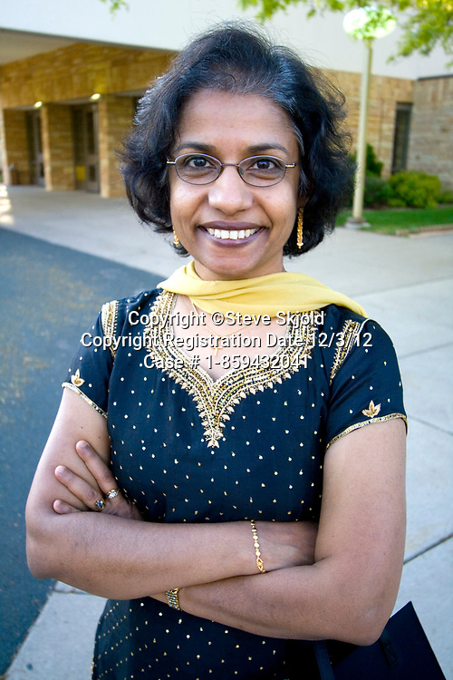 Happy East Indian American woman age 57 wearing an ethnic stylish dress at her sisters wedding. Minneapolis Minnesota MN USA