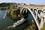 Fishing boat passing under arch bridge at Depoe Bay, worlds most narrow natural harbor entrance, Central Oregon Coast