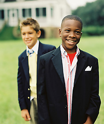 two boys dressed in blue blazers outdoors on a lawn