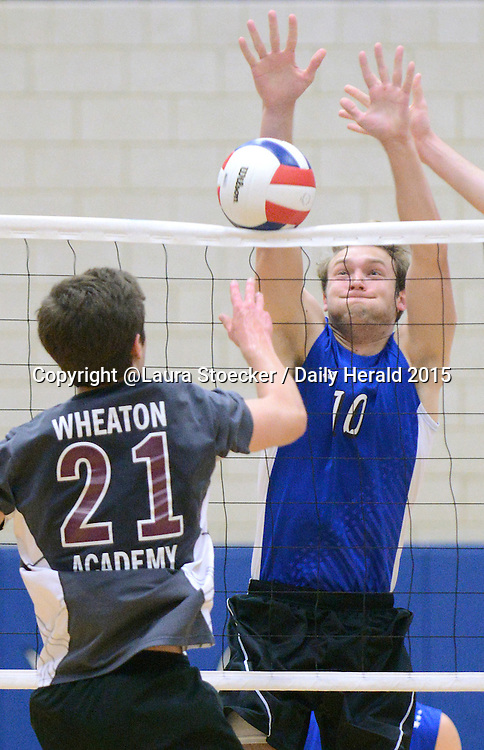 Laura Stoecker/lstoecker@dailyherald.com<br /> Geneva's Spencer Sharpe blocks a spike by Wheaton Academy in the first match of the regional semifinals at Geneva High School Tuesday.