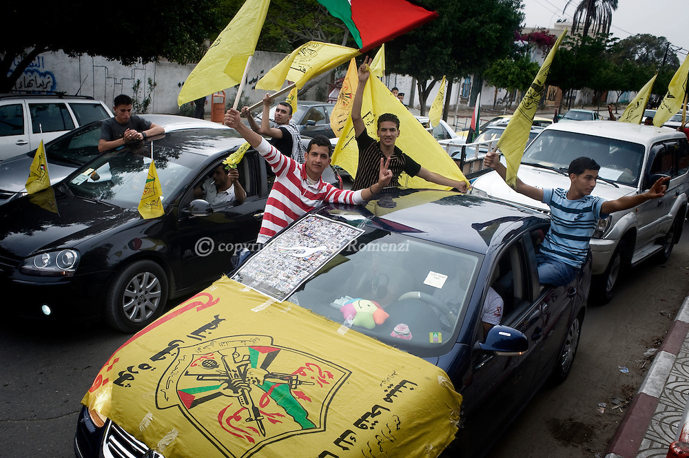 GAZA CITY : Palestinians wave Fatah flags as they celebrate the unity deal between rival factions Hamas and Fatah on May 4, 2011 at the Unknown Soldier square in Gaza City where the yellow flag was allowed to be seen for the first time since 2007 as a reconciliation deal was signed by the rival movements in Cairo.ALESSIO ROMENZI