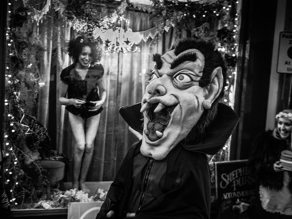 Female partly clad model in shop window in Whitby North Yorkshire with grotesque Dracula character walking past. Afternoon daylight.