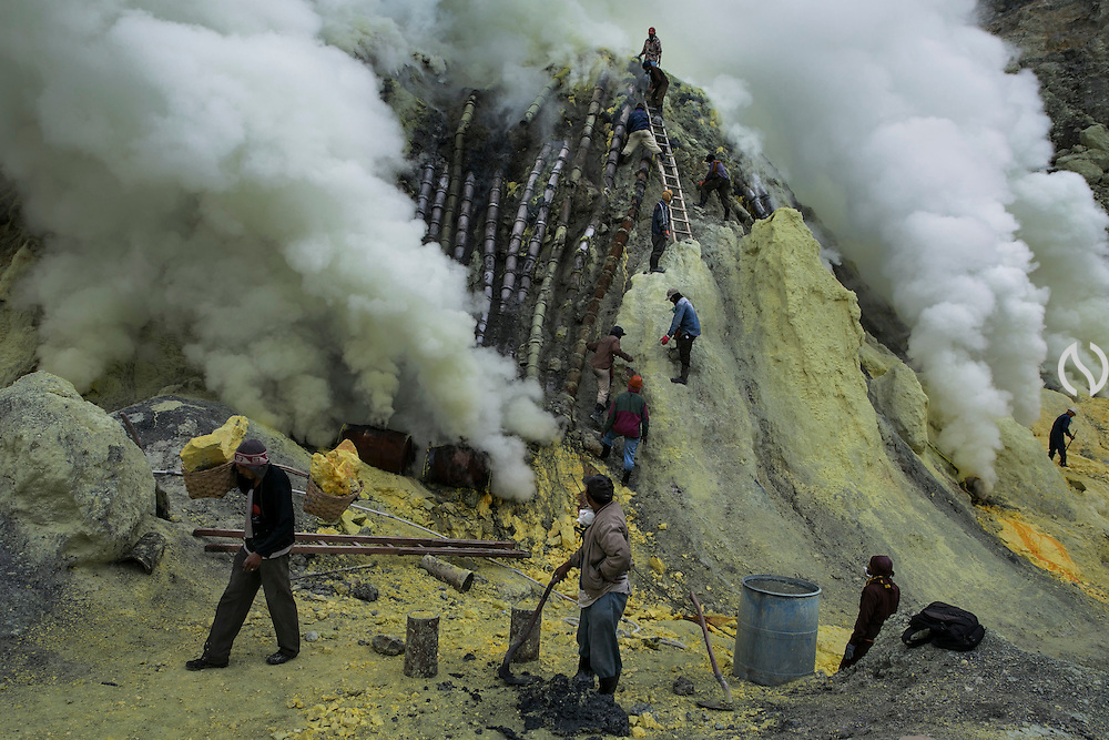 BONDOWOSO, EAST JAVA - DECEMBER 17: Sulfur miners work at Ijen crater during annual sacrificial ritual in Bondowoso, East Java, Indonesia, December 17, 2013. The miners held the sacrifice in order to ask blessing of good result and prevent from accident or injury. The tradition begun in 1978 after a tragedy that killed four people and fourteen black out cause of poisoning gas. Daily miners produce fifteen ton of sulfur or approximately 450 ton a month. Come close to 150 miners work everyday. All the sulfur goes to sugar factory ans used as sugar whitening.