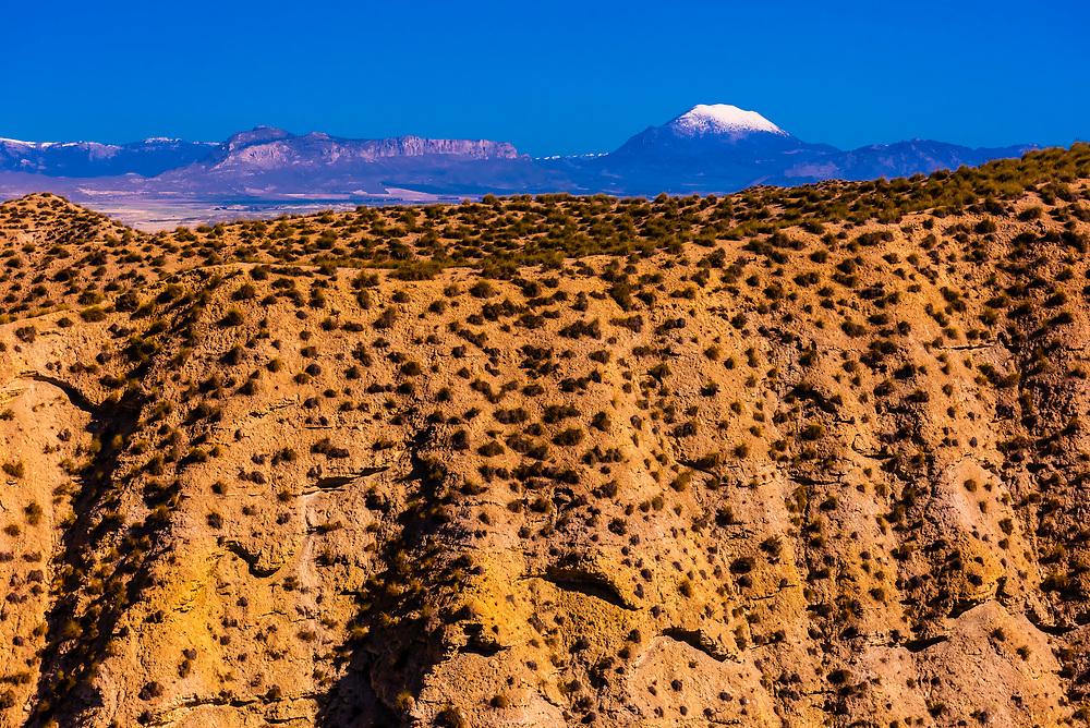 Badlands, seen from the Mirador Cueva los Amos viewpoint with snowcapped La Sagra peak in background, near Galera,Granada Province, Andalusia, Spain.