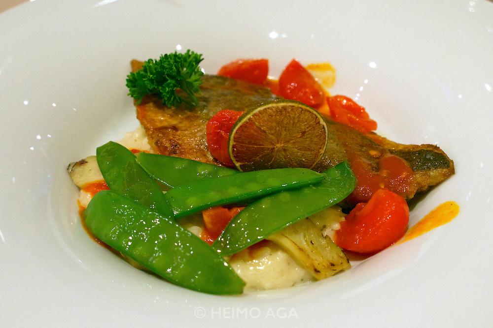Längenfeld, Tyrol, Austria. AQUA DOME. Dinner at the restaurant.<br /> Filet von der Dorade auf Artischockenrisotto mit sautierten Zuckerbesenschoten und Paradeisersalsa.