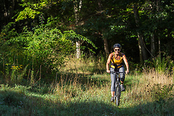 A woman rides her mountain bike on Sagamore Hill in Hamilton, Massachusetts.