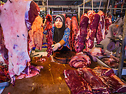 19 NOVEMBER 2014 - BANGKOK, THAILAND: A Muslim shopkeeper butchers goat meat in Khlong Toei Market in Bangkok. Between July and September the economy expanded just 0.6 percent compared to the previous year, the National Economic and Social Development Board (NESDB) reported. Thailand's economy achieved a weak 0.2 per cent growth across the first nine months of the year. The NESDB said the Thai economy is expected to grow by 1 percent in 2014. Authorities say the sluggish growth is because tourists have not returned to Thailand in the wake of the coup in May, 2014, and that reduced demand for computer components, specifically hard drives, was also hurting the economy. Thailand is the leading manufacturer of computer hard drives in the world. The Thai government has announced a stimulus package worth $11 billion (US) to provide cash handouts to farmers and promised to speed up budget spending to boost consumption.   PHOTO BY JACK KURTZ