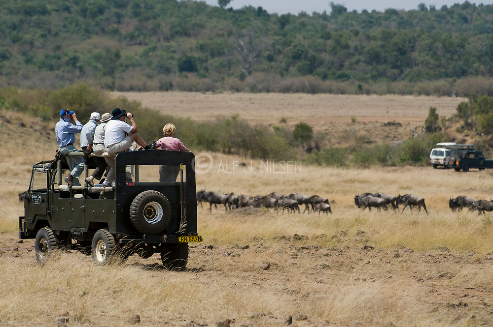 Tourists watching the annual great wildebeest migration in Maasai Mara, Kenya.