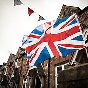 A Union Jack (also known as the Union Flag) flies in the breeze on an overcast day in a residential street in Wells, Somerset.