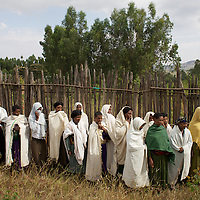 Women from the village of Mecha watch a demonstration while keeping some distance from hives at the Ambrosia beekeeping demonstration and training centre in Mecha.<br /> <br /> Harvesting honey supplements the income of small farmers in the Ethiopian region of Amhara where there is a long tradition of honey production. However, without the resources to properly invest in production and the continued use of of traditional, low-yielding hives, farmers have not been able to reap proper reward for their labour. <br /> <br /> The formation of the Zembaba Bee Products Development and Marketing Cooperative Union is an attempt to realize the potential of honey production in Amhara and ensure that the benefits reach small producers. <br /> <br /> By providing modern, high-yield hives, protective equipment and training to beekeepers, the Cooperative Union helps increase production and secure a steady supply of honey for which there is growing demand both in and beyond Ethiopia. The collective processing, marketing and distribution of Zembaba's &quot;Amar&quot; honey means that profits stay within the cooperative network of 3,500 beekeepers rather than being passed onto brokers and agents. The Union has signed an agreement with the multinational Ambrosia group to supply honey to the export market. <br /> <br /> Zembaba Bee Products Development and Marketing Cooperative Union also provides credit to individual members and trains carpenters in the production of modern hives. <br /> <br /> Photo: Tom Pietrasik<br /> Mecha, Amhara. Ethiopia<br /> November 17th 2010