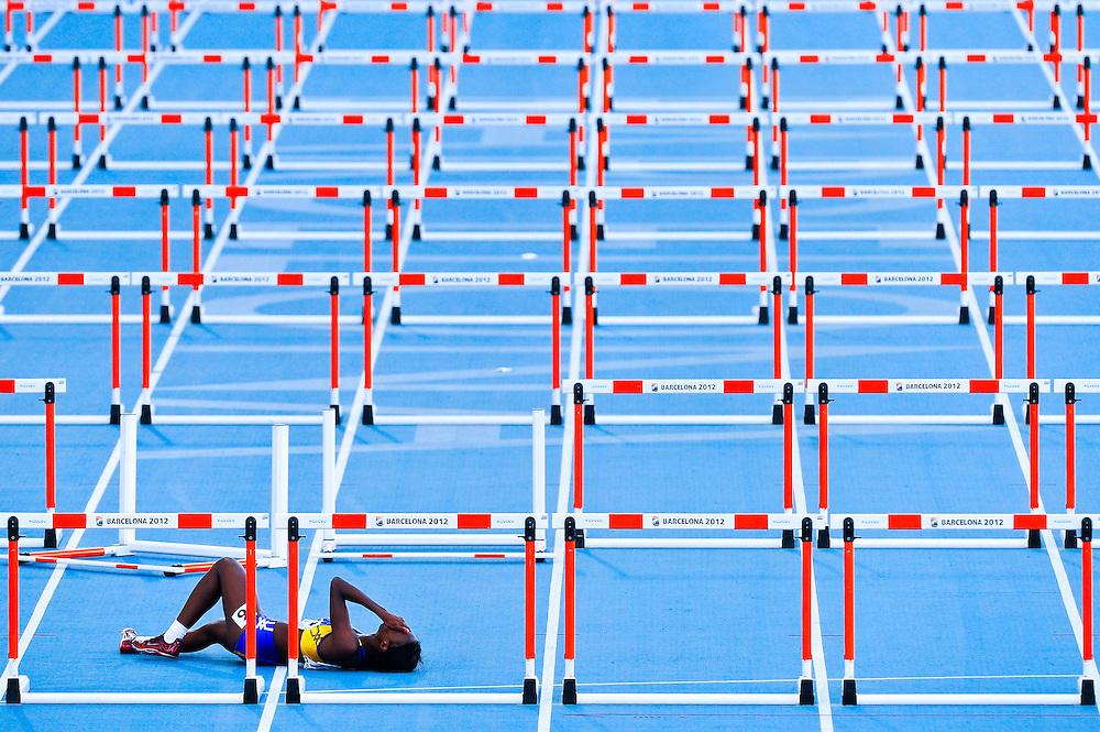 Sade Mariah Greenidge de Barbados se lamenta en el suelo tras caer en la penúltima valla en la semifinal de los 100 metros vallas femeninos en el quinto día de los 14º IAAF Mundiales Junior de Atletismo en el Estadio Olímpico Lluis Companys de Barcelona, España el 14 de Julio del 2012.