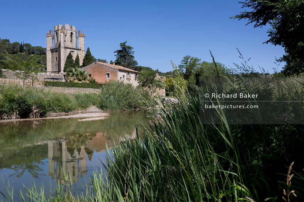 The Abbey of Sante-Marie D'Orbieu in the pretty French medieval walled village of Lagrasse on the River Orbieu, on 24th May, 2017, in Lagrasse, Languedoc-Rousillon, south of France. Lagrasse is listed as one of France's most beautiful villages and lies on the famous Route 20 wine route in the Basses-Corbieres region dating to the 13th century.