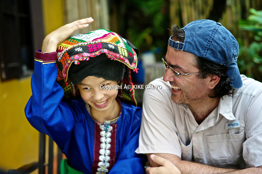 Photographer Kike Calvo with teen girl wearing Tai Dam traditional dress in Laos. Its used in Luang Prabang province.