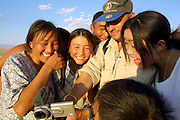 GOBI DESERT, MONGOLIA..08/30/2001.Tsagan Bulag, gers belonging to the family of 15-year-old Urna (m.), winner of a gold medal in an English language school competition..Paul Friedrich, German travel agent, showing video of his trying to help them milk goats..(Photo by Heimo Aga).